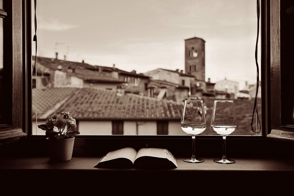 Window view with flower pot, book, wine and historic buildings background in Lucca Italy