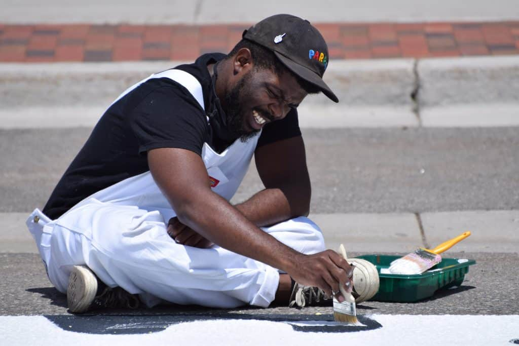 Johnny Draco paints the letter B in the Black Lives Matter mural Tuesday, July 14, with birds that symbolize freedom. Draco is part of the Denver-based design company Realize.