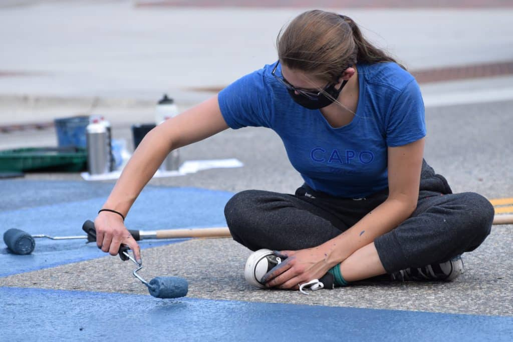 Devon Galpin Clarke of Frisco adds blue to the R of the Black Lives Matter mural on Frisco's Main Street on Tuesday, July 14. The finished letter is dotted with white animal prints in honor of her nonprofit, Endangered Activism, that she co-founder with her mother, Shannon Galpin.