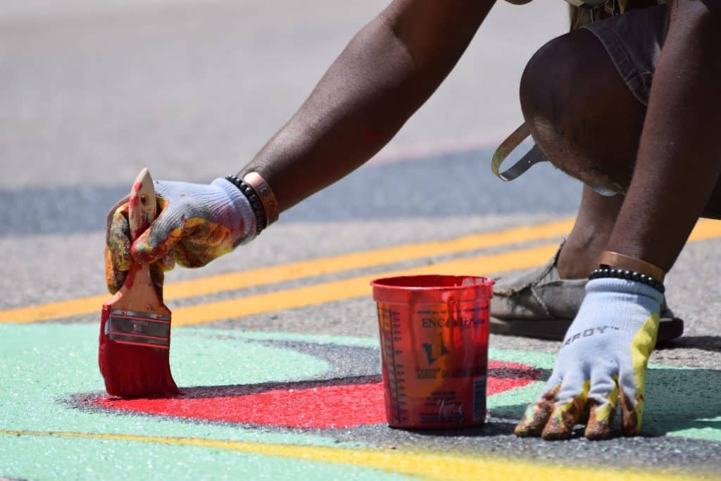 """Muralist Aaron Sutton, known as Visual Goodies, paints the C of the Black Lives Matter mural on Frisco's Main Street on Tuesday, July 14. The Denver-based artist is known for his """"Afro-cosmic"""" pieces."""